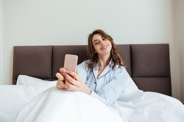 Heureuse jeune femme vêtue de pyjama faire selfie.
