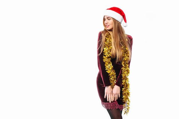 Heureuse jeune femme vêtue d'une robe et bonnet de noel