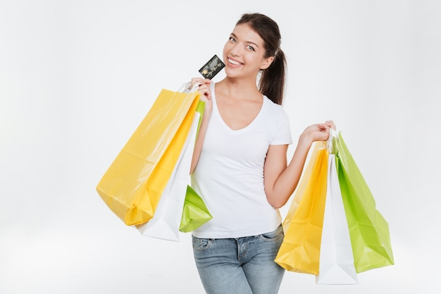 Heureuse jeune femme vêtue d'un t-shirt blanc tenant des achats et une carte de crédit après le shopping