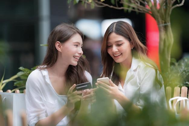 Heureuse jeune femme avec visage souriant parler et rire tenant une carte de crédit et à l'aide de téléphone avec centre commercial de communication