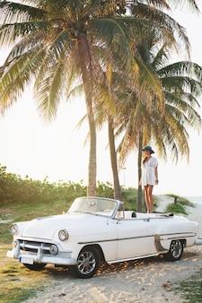 Heureuse jeune femme et voiture décapotable rétro à côté de la plage de la ville de varadero