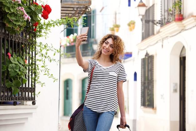 Heureuse jeune femme de voyage prenant selfie à l'extérieur