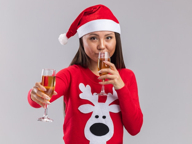 Heureuse jeune fille asiatique portant un chapeau de noël avec un pull tenant une coupe de champagne et des boissons isolées sur fond blanc