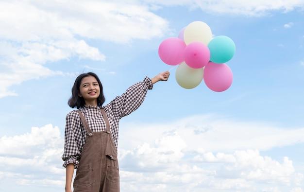 Heureuse jeune fille asiatique tenant des ballons colorés