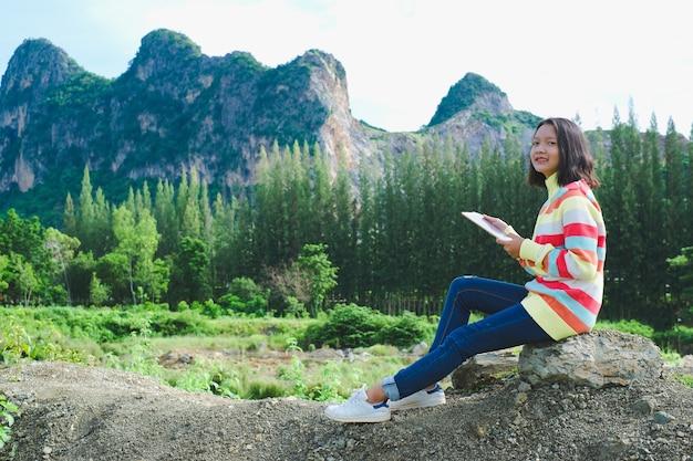 Heureuse jeune fille assise sur fond de nature.