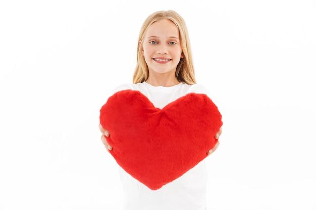 Heureuse jeune fille blonde dans des vêtements décontractés donnant coeur de joie sur blanc