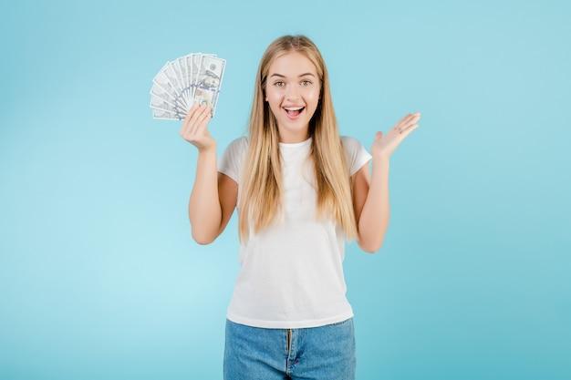 Heureuse jeune fille blonde avec un dollar en argent à la main, isolée sur bleu