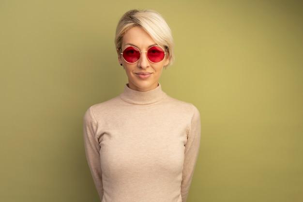 Heureuse jeune fille blonde portant des lunettes de soleil gardant les mains derrière le dos isolées sur un mur vert olive avec espace pour copie