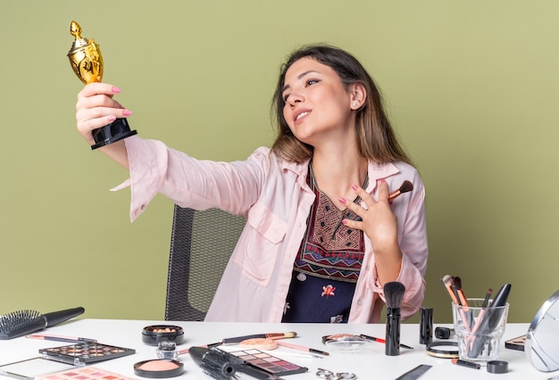 Heureuse jeune fille brune assise à table avec des outils de maquillage tenant un pinceau de maquillage et regardant la coupe gagnante isolée sur un mur vert olive avec espace pour copie