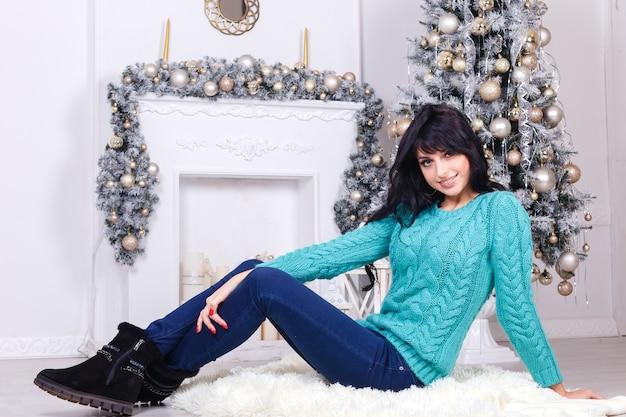 Heureuse jeune fille brune aux cheveux longs, assis sur un sol à l'intérieur dans un intérieur décoré de noël.