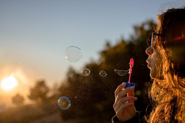 Heureuse jeune fille avec des bulles de savon en automne au coucher du soleil.