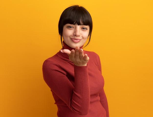 Heureuse jeune fille caucasienne brune envoie un baiser avec la main isolée sur un mur orange avec espace de copie
