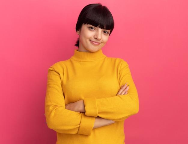 Heureuse jeune fille caucasienne brune se tient les bras croisés isolés sur un mur rose avec espace pour copie