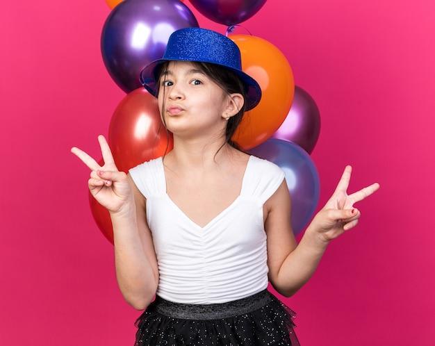 Heureuse jeune fille caucasienne avec chapeau de fête bleu debout devant des ballons à l'hélium gesticulant signe de victoire isolé sur mur rose avec espace de copie