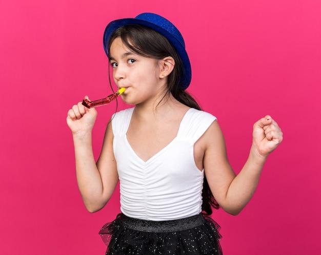 Heureuse jeune fille caucasienne avec un chapeau de fête bleu soufflant un sifflet de fête en gardant les poings isolés sur un mur rose avec espace de copie