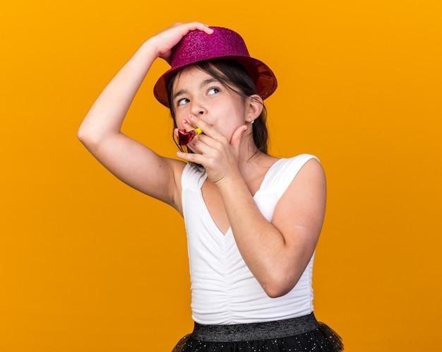 Heureuse jeune fille caucasienne tenant un chapeau de fête violet sur la tête et soufflant un sifflet de fête regardant le côté isolé sur un mur orange avec un espace de copie
