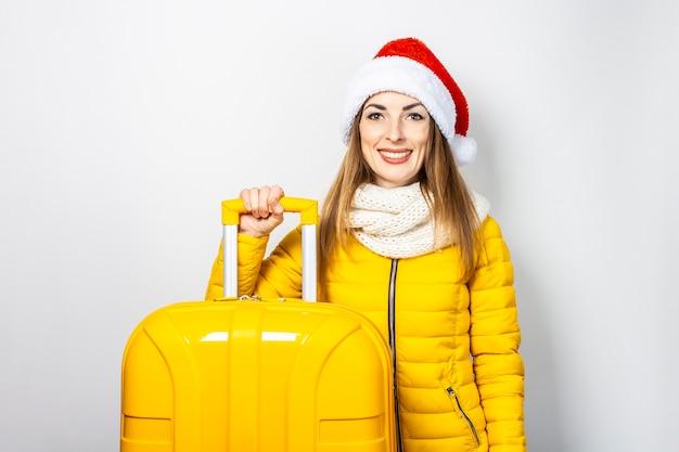 Heureuse jeune fille dans une veste jaune et un chapeau de père noël tient une valise jaune