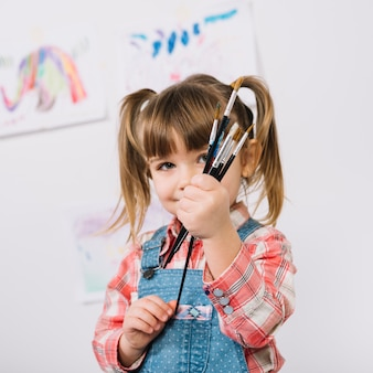Heureuse jeune fille debout avec des pinceaux dans les mains
