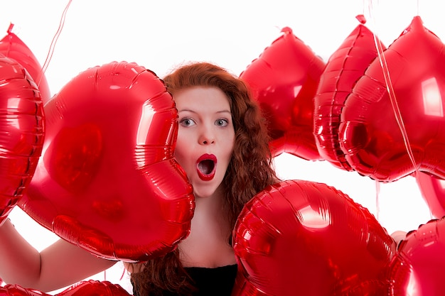 Heureuse jeune fille entre ballons coeur rouge
