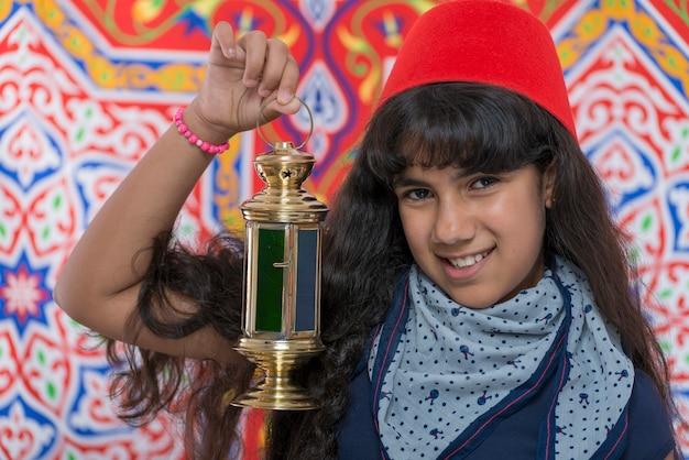 Heureuse jeune fille avec fès et lanterne célébrant le ramadan