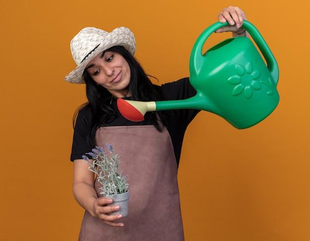 Heureuse jeune fille de jardinier caucasienne en uniforme et chapeau arrosant des fleurs dans un pot de fleurs avec arrosoir