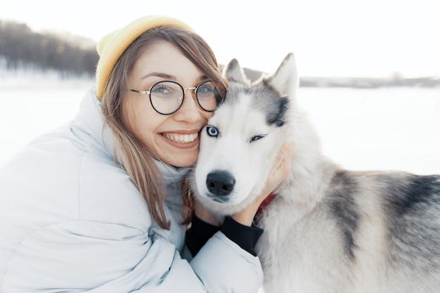 Heureuse jeune fille jouant avec un chien husky sibérien à winter park