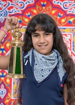 Heureuse jeune fille avec lanterne célébrant le ramadan