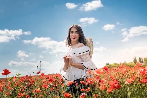 Heureuse jeune fille mince marche dans le champ de coquelicots rouges