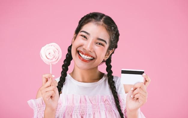 Heureuse jeune fille montrant la carte de crédit avec des bonbons sur fond rose