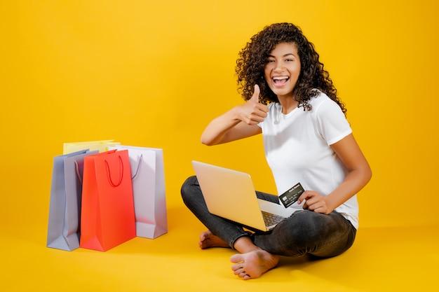 Heureuse jeune fille noire avec des sacs colorés assis avec ordinateur portable et carte de crédit isolé sur jaune