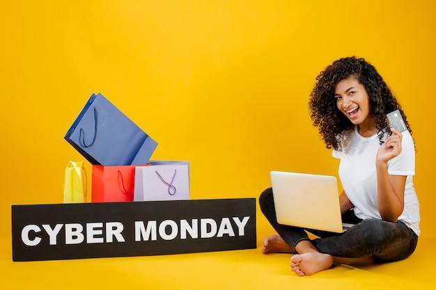 Heureuse jeune fille noire avec des sacs colorés et signe de lundi cyber assis avec un ordinateur portable et carte de crédit isolé sur jaune