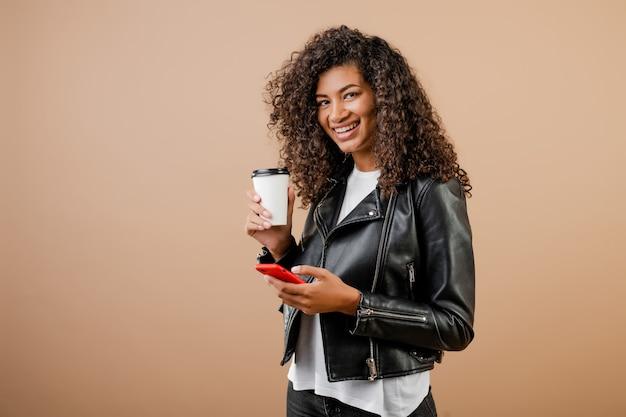 Heureuse jeune fille noire souriante avec téléphone et café pour aller tasse isolé sur marron