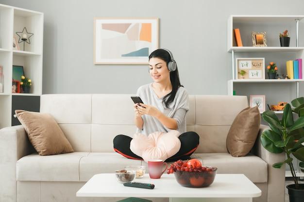 Heureuse jeune fille avec un oreiller portant des écouteurs tenant et regardant le téléphone assis sur un canapé derrière une table basse dans le salon