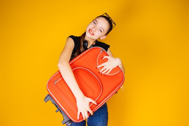 Heureuse jeune fille partant en vacances, aventure, tenant une grosse valise rouge