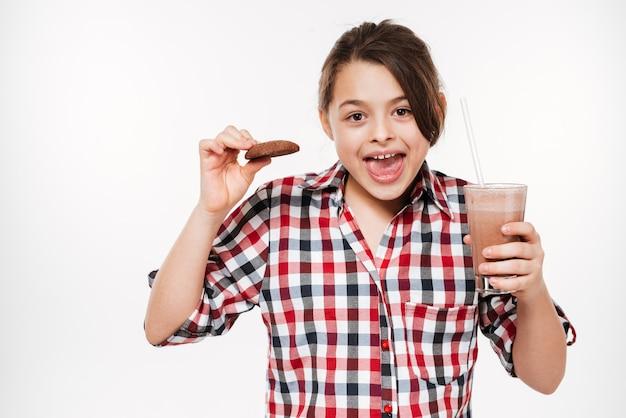 Heureuse jeune fille posant avec cookie et cacao