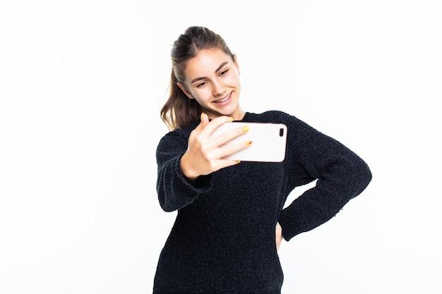 Heureuse jeune fille prenant des photos d'elle-même par téléphone portable sur mur blanc