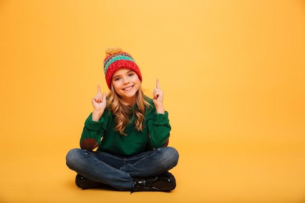 Heureuse jeune fille en pull et chapeau assis sur le sol tout en pointant vers le haut et en regardant la caméra sur orange
