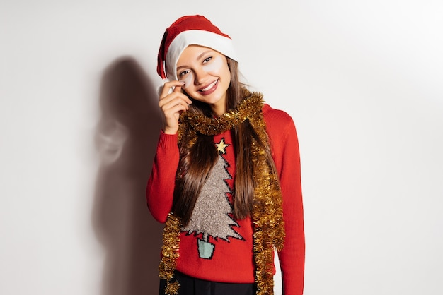 Heureuse jeune fille en pull de noël rouge fête noël, sous les yeux
