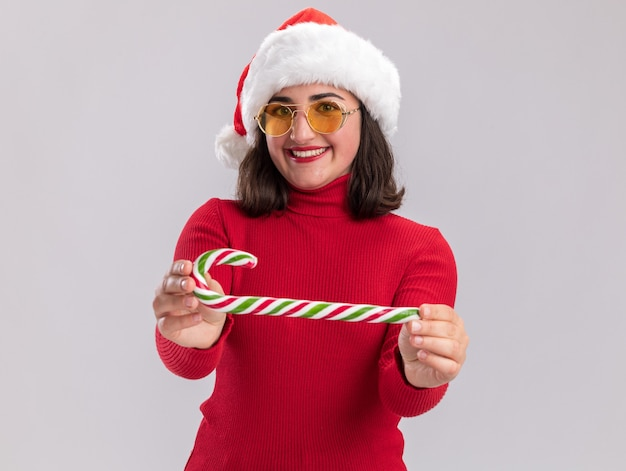 Heureuse jeune fille en pull rouge et bonnet de noel portant des lunettes tenant une canne en bonbon regardant canera avec sourire sur le visage debout sur fond blanc