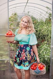Heureuse jeune fille avec récolte de tomates en serre