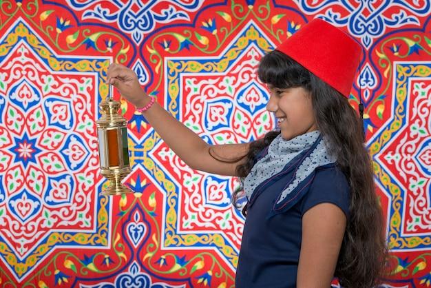 Heureuse jeune fille regardant la lanterne célébrant le ramadan