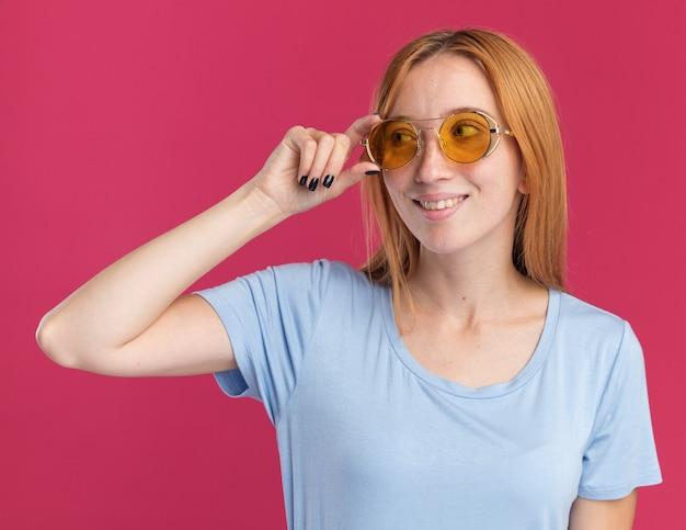 Heureuse jeune fille rousse au gingembre avec des taches de rousseur dans des lunettes de soleil regardant de côté