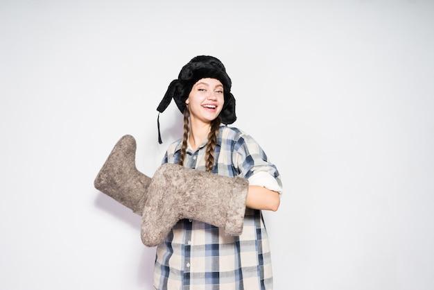 Heureuse jeune fille russe dans un chapeau de fourrure noire se réjouit en hiver, garde des bottes de feutre chaudes