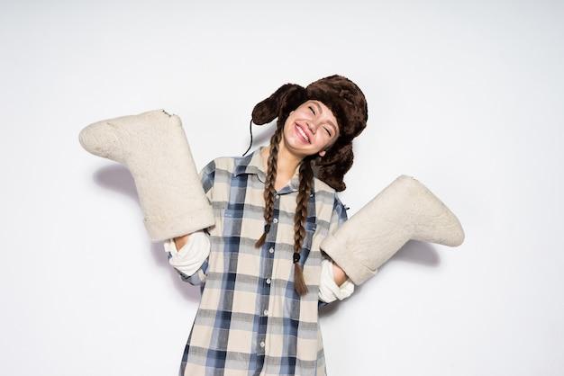 Heureuse jeune fille de russie dans un chapeau de fourrure chaud se réjouit en hiver, garde des bottes de feutre chaudes