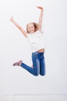 Heureuse jeune fille sautant par-dessus un fond blanc