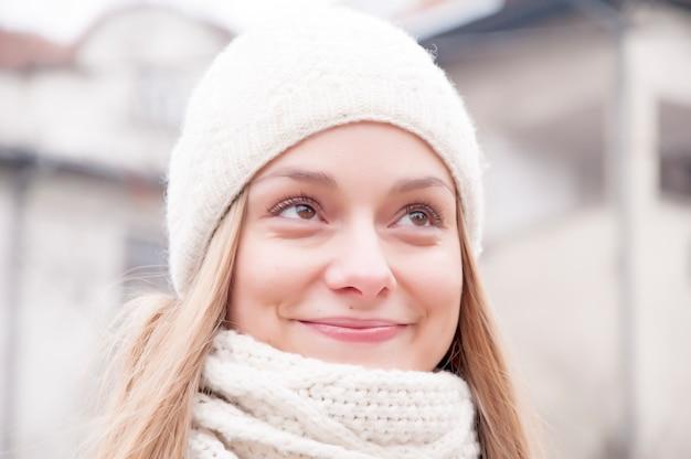 Heureuse jeune fille se réchauffant dans des vêtements d'hiver chauds.