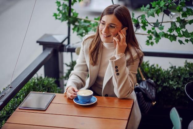 Heureuse jeune fille souriante assise à la cafétéria, buvant son café et parlant au téléphone.