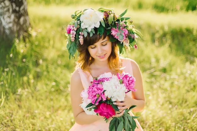Heureuse jeune fille souriante avec une couronne de fleurs et un bouquet de pivoines sur une journée d'été ensoleillée