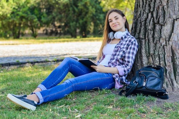 Heureuse jeune fille souriante dans des vêtements décontractés avec des écouteurs sur le cou, assise sur l'herbe et livre de lecture