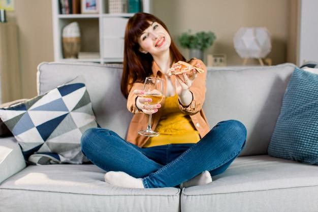 Heureuse jeune fille souriante en jeans et chemise jaune, tenant un verre de vin et un morceau de pizza, assis sur un canapé gris dans une chambre confortable
